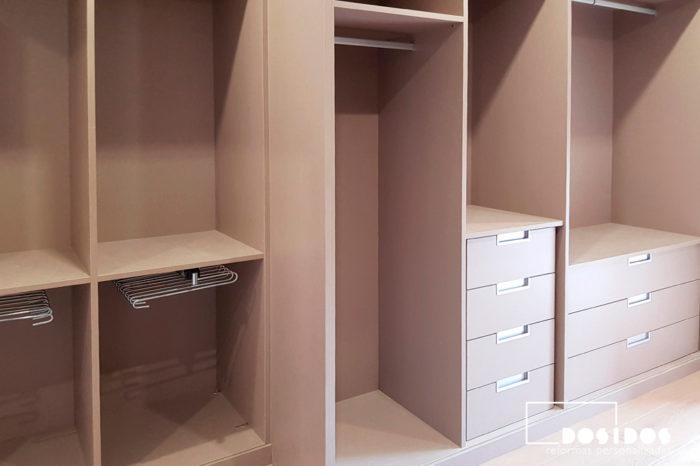 Vestidor marrón abierto con mucho almacenaje, accesorios pantaloneros, cajones y barras de colgar dentro de la habitación de matrimonio.