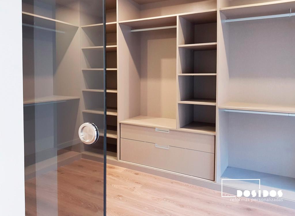 Detalle de la puerta corredera de vidrio ahumado de acceso al vestidor con módulos en ele y gran almacenaje.