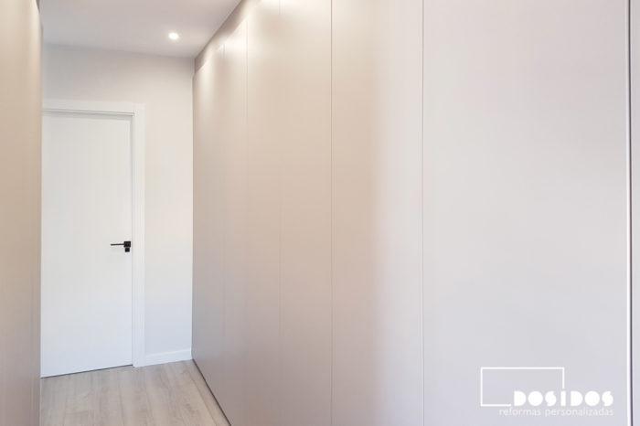 Armario vestidor cerrado con puertas abatibles lisas color cachemir, suelo parquet y puerta del baño al fondo color blanco.