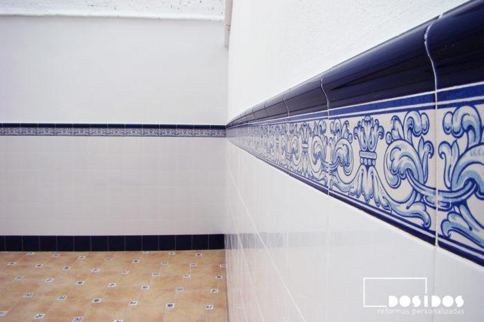 Detalle de la zocalada de azulejo Valenciano, blanco con cenefa dibujos azules. Colocada a media altura en una terraza.