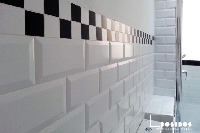 Detalle de los azulejos blancos biselados 10x20 y cenefa decorativa negra.