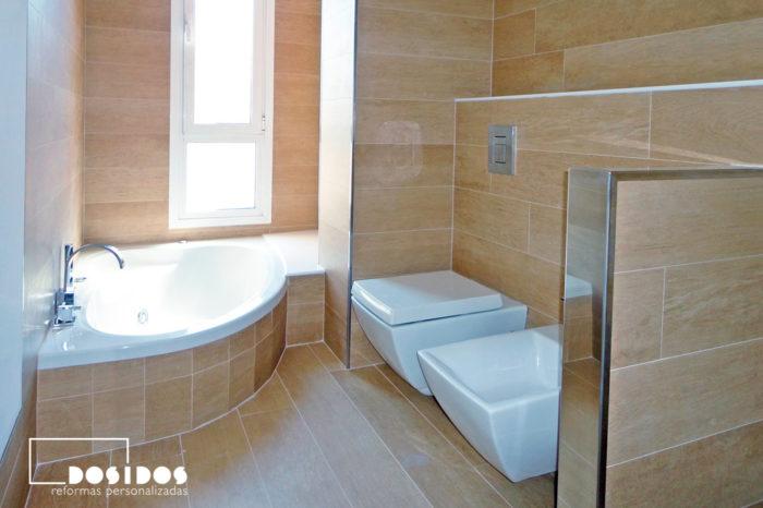 Reforma de baño alicatado con azulejo madera, bañera hidromasaje y sanitarios suspendidos