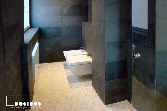 Baño negro con suelo piedra natural y sanitarios suspendidos