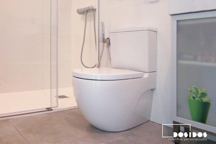 Baño pequeño azulejos blancos y marrones, detalle del inodoro meridian y ducha.