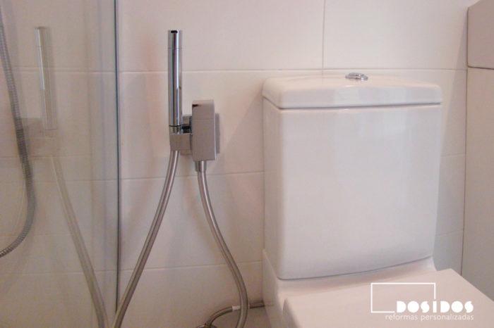Baño azulejos blancos y detalle grifo bidé wc junto al inodoro.