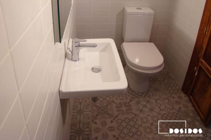 Baño pequeño vintage con un lavabo de porcelana pequeño suspendido, inodoro y azulejos grises con dibujos de vives cerámica.