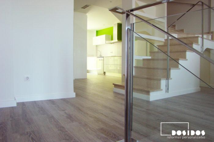 Barandilla de la escalera realizada en acero inoxidable y vidrio transparente. Cocina abierta al salón.
