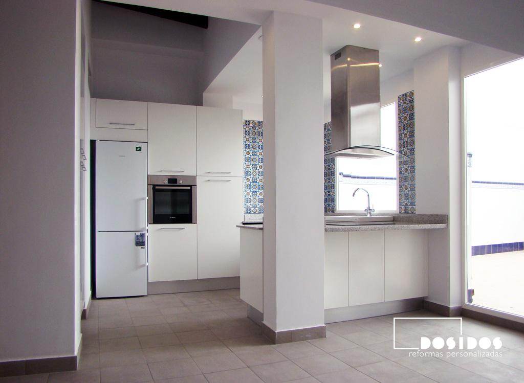 Reforma de cocina blanca abierta al salón con isla muy luminosa, vista a la terraza.