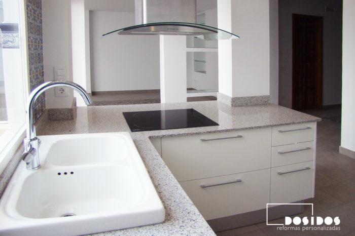 Detalle de una cocina abierta en U al salón con barra. Muebles blancos y fregadero de porcelana.