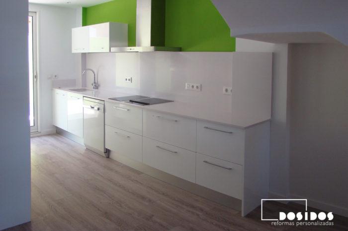 Cocina abierta con muebles y encimera blanca. Paredes pintadas en color verde y suelo parquet sintético.