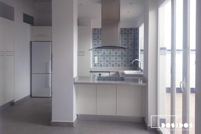 Reforma de una cocina abierta al salón con barra. Muebles de color blanco y azulejos dibujos azules.