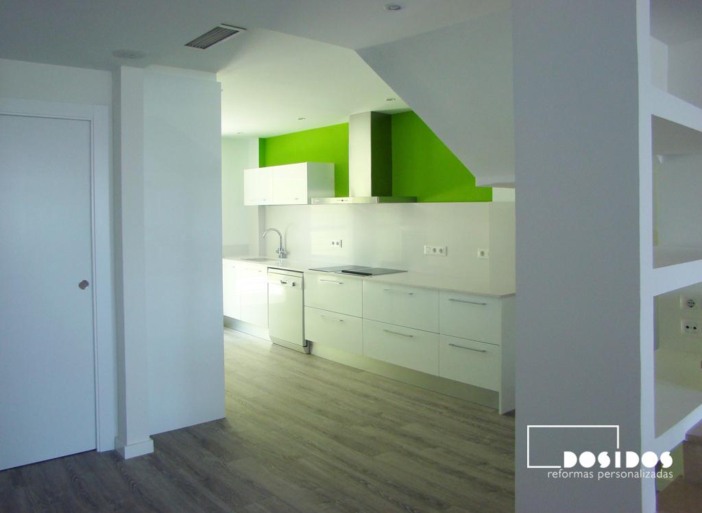 Cocina blanca y verde, abierta al salón, separada por estantería de escayola en el hueco de la escalera.