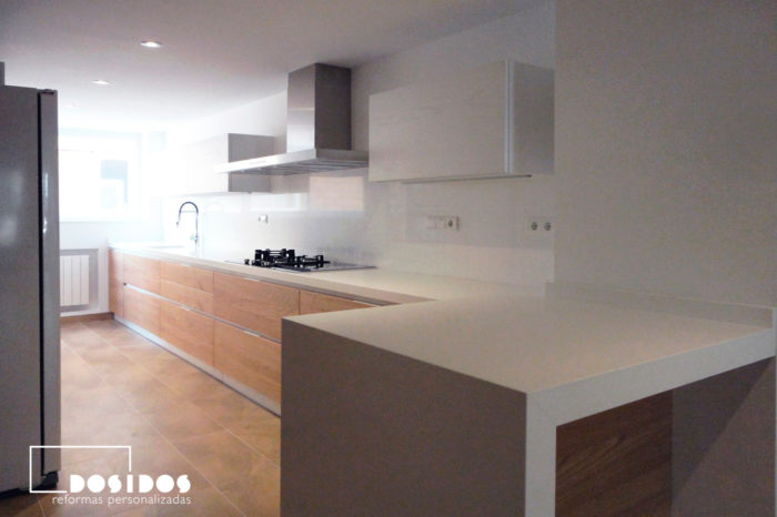 Cocina abierta y barra con muebles de madera y blancos con encimera blanca