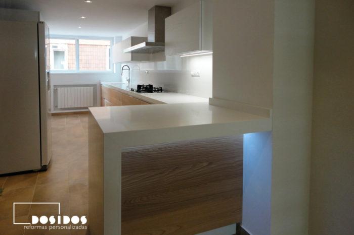 Cocina abierta y barra con iluminación Led con muebles de madera y encimera blanca