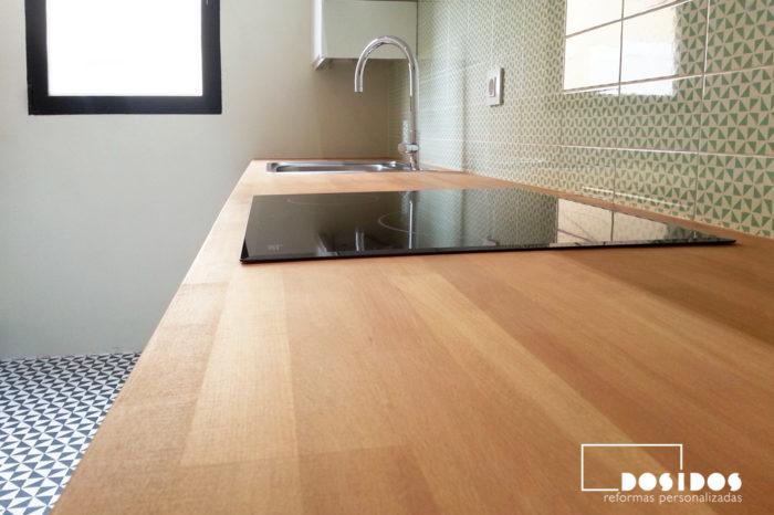 Encimera de cocina de madera, frente de azulejos verdes con dibujo vintage y vitrocerámica.