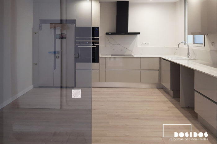 Reforma cocina grande en forma de L, con puerta corredera exterior vidrio gris, campana extractora negra, muebles grises y con encimera blanca