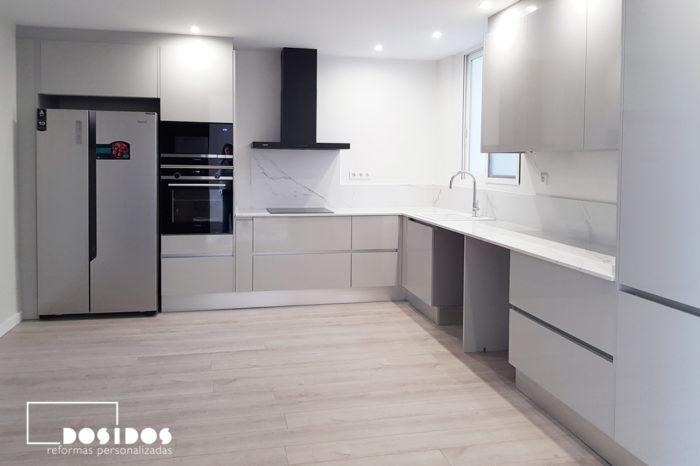 Reforma de cocina grande en forma de L con muebles grises, encimera de cocina blanca y campana extractora decorativa negra. Frigorífico americano con dos puertas. Suelo parquet sintético color gris