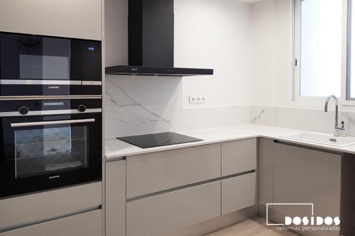 Cocina en L, campana extractora negra, muebles de cocina grises y con encimera blanca