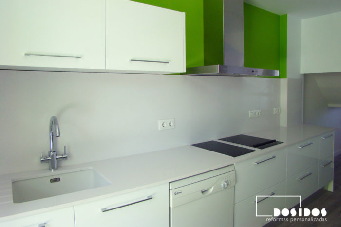 Cocina abierta al salón con muebles y encimera blanca. Paredes pintadas en color verde.