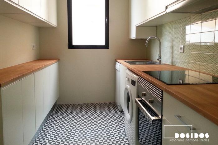 cocina pequeña estilo vintage, con dos encimeras de madera, muebles blancos y frente de azulejos verdes con dibujos.