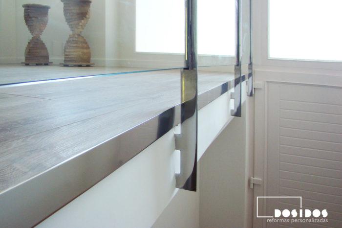Detalle de la barandilla de la escalera realizada en acero inoxidable y vidrio transparente.
