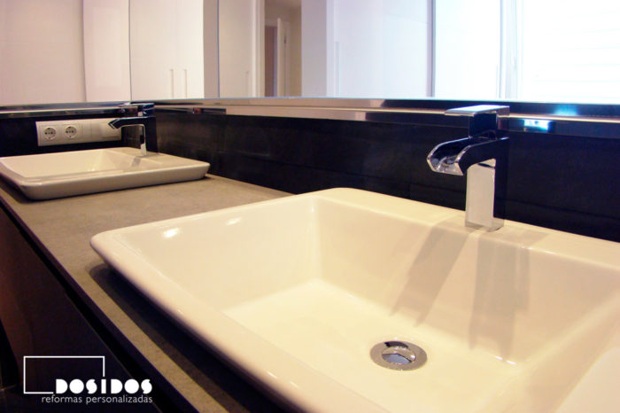 Detalle de dos lavabos en mueble con grifos cromados en cascada de un baño suite