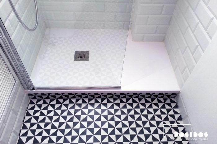 Plato de ducha con el suelo en azulejos blancos y negros dibujo triángulos.