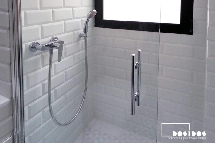 Grifos de ducha y mampara abatible transparente con azulejos blancos biselados 10x20 mate.