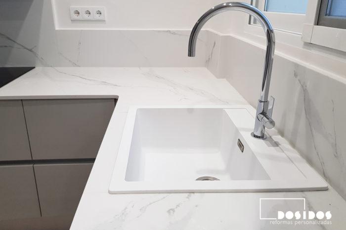 Detalle del fregadero de cocina blanco y el grifo cromado caño alto curvo. Encimera de cocina blanca.