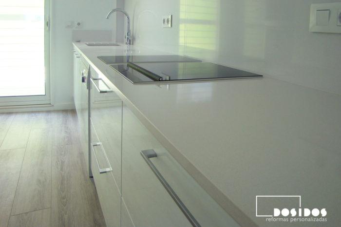 Detalle de encimera de cocina blanca con suelo de parquet sintético.