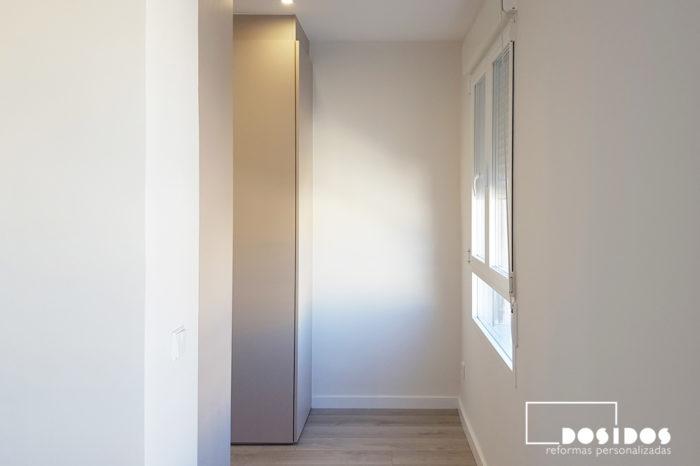 Entrada al vestidor cerrado con puertas abatibles lisas color cachemir por el lateral del cabezal de la habitación de matrimonio