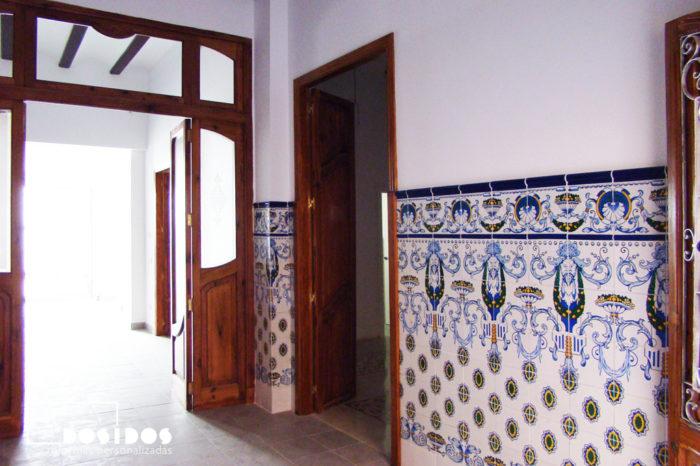 Entrada de casa de pueblo con zocalada de azulejo Valenciano con dibujos en color azul. Detalle de las puertas de madera de gran tamaño.