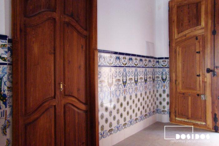 Entrada de una casa de pueblo con zocalada de azulejo Valenciano alicatado a media altura con dibujos. Dos grandes puertas de madera