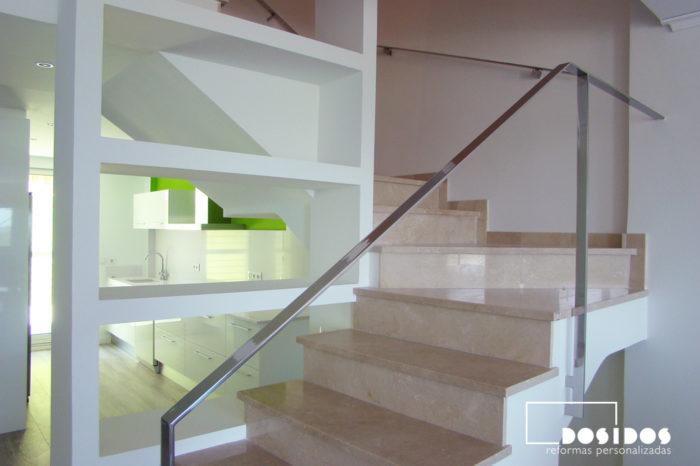 Estantería de escayola en el hueco de la escalera con barandilla inox y peldaños de mármol.