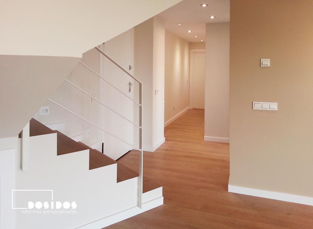 Reforma vivienda ático duplex, detalle de la escalera forrada de madera y barandilla de hierro color blanco.
