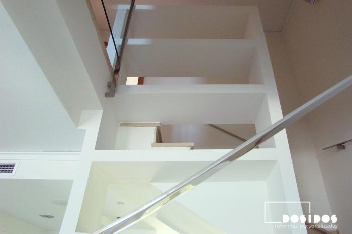 Hueco de escalera con estantes de escayola y barandilla de inox.