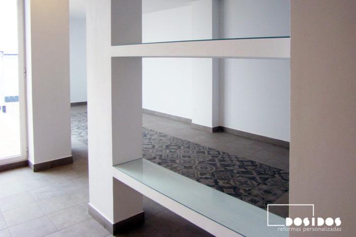 Separación de ambientes en una salón con una estantería de escayola y cristal.