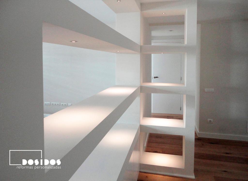 Estanterías de pladur blancas con iluminación que sirven para separar el salón del recibidor