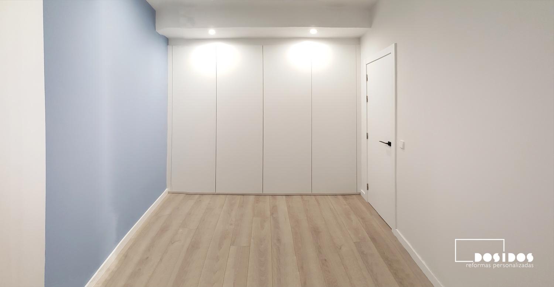 Habitación infantil blanca y azul con el suelo parquet, armario y puerta en color blanco.