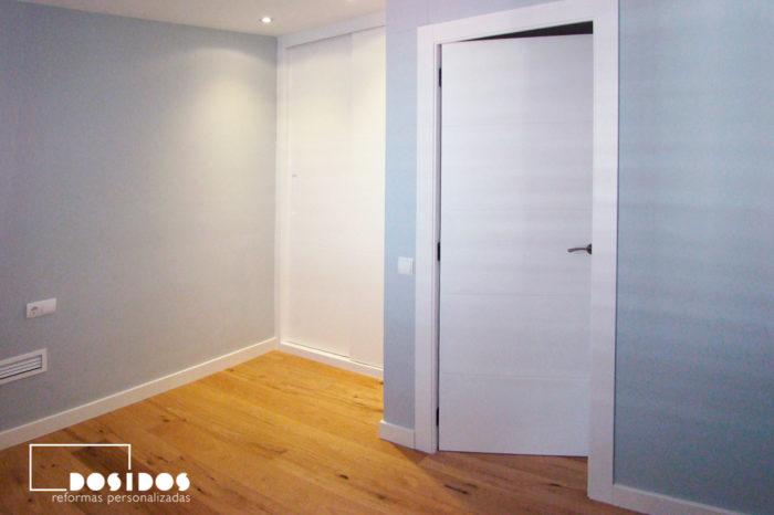 Habitación infantil azul con puerta y armario blanco