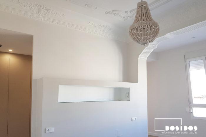 Habitación de matrimonio en suite donde vemos el tabique cabezal con estante y la entrada al vestidor, conservando los techos altos con molduras.