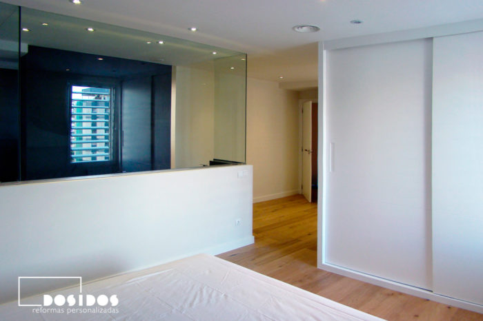Habitación suite con vestidor y tabique de separación con el baño de cristal