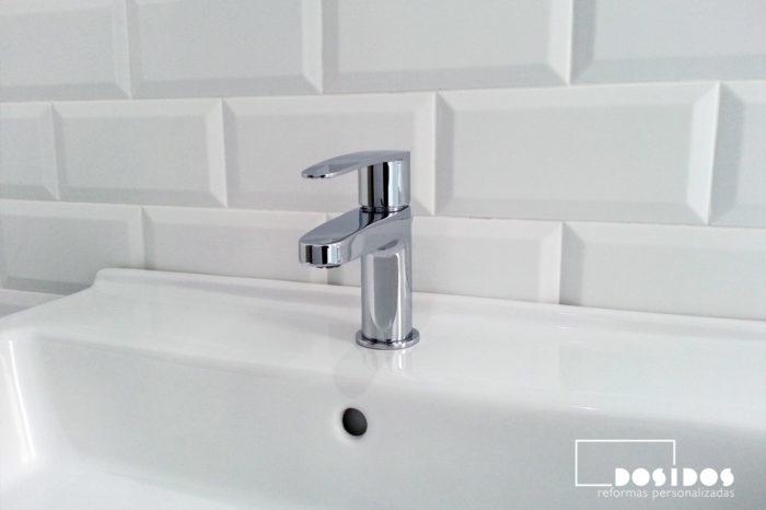 Detalle de grifo de lavabo del baño con azulejos blancos biselados 10x20 mate.
