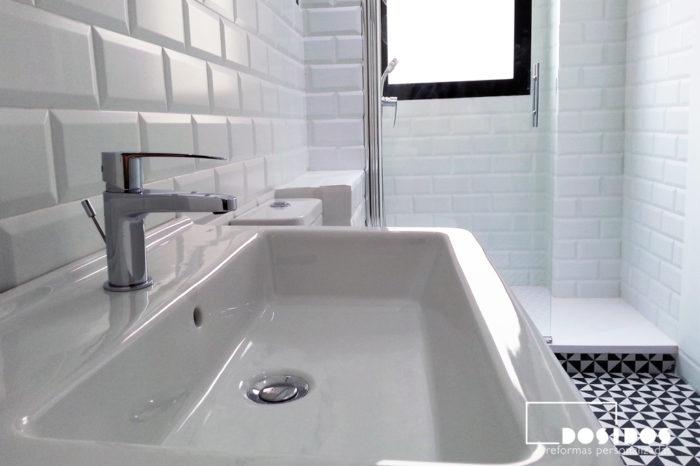 Detalle de lavabo del bano estilo vintage con azulejos blancos biselados.