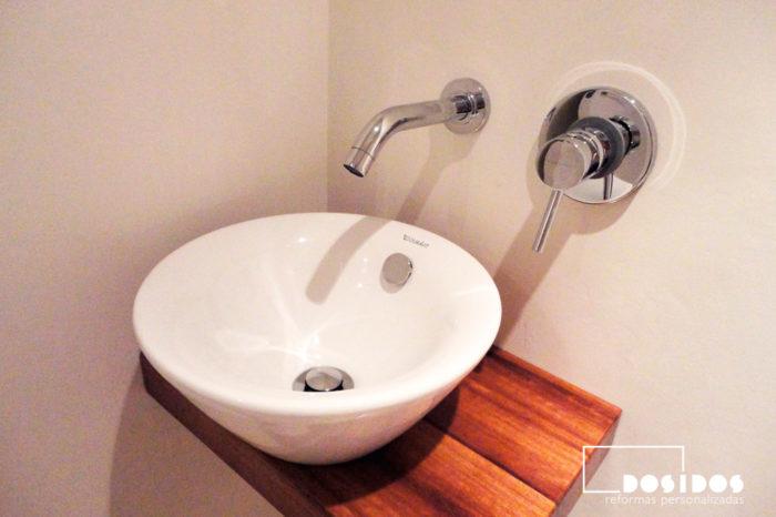 Lavabo sobre encimera de madera con grifo a pared para un baño pequeño