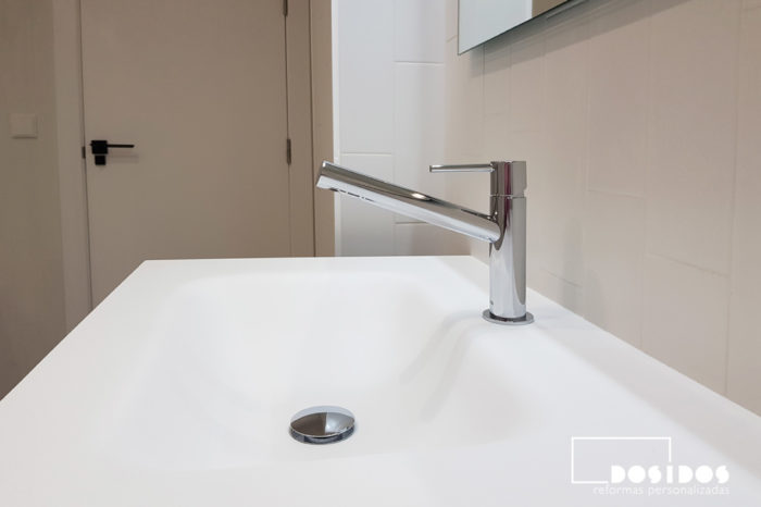Detalle del lavabo en mueble fabricado en krion blanco con el grifo cromado