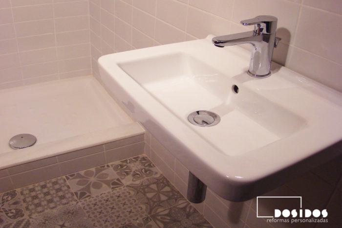 Vista de un lavabo de porcelana pequeño suspendido, ducha y suelo gris con dibujos de vives cerámica.