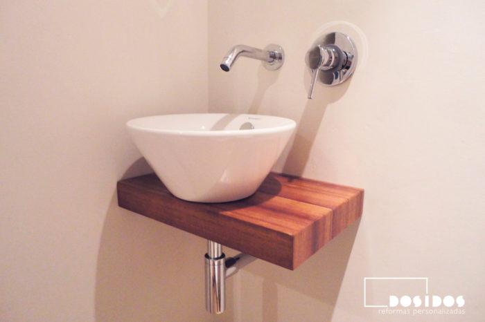 Lavabo sobre encimera de madera suspendido con grifo a pared para un baño pequeño