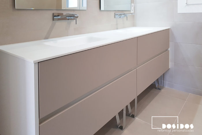 Mueble de cuarto de baño moderno, cuatro cajones color topo / visón, dos lavabos fabricados en krion con grifos a pared. Patas cromadas