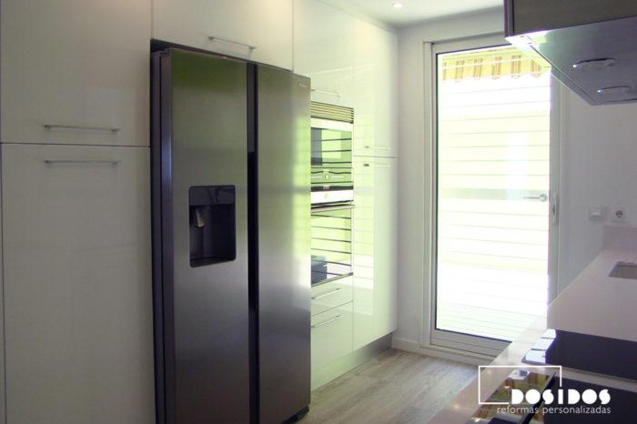 Cocina con muebles columna de almacenaje de color blanco y frigorífico americano. Puerta de aluminio corredera interior salida a la terraza.
